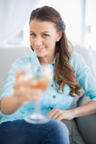Smiling woman showing glass of white wine Royalty Free Stock Photography