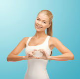 Smiling woman showing heart shape gesture Royalty Free Stock Image