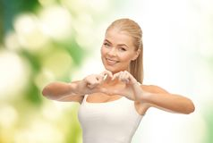 Smiling woman showing heart shape gesture Royalty Free Stock Images