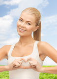 Smiling woman showing heart shape gesture Royalty Free Stock Photography