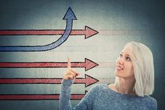 Different thinking. Smiling woman showing imaginative arrows with index finger one change direction bending and going up. Different business thinking, creativity Stock Photos