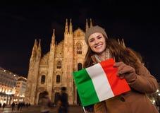 Smiling woman showing Italian flag near Duomo in evening, Milan Royalty Free Stock Photos