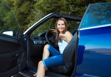 Smiling woman showing key in a cabriolet car Royalty Free Stock Photography