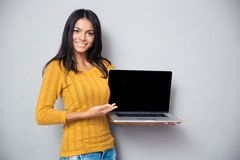 Smiling woman showing laptop screen Stock Photography