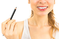 Smiling woman showing a make up pencil Royalty Free Stock Photo