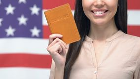 Smiling woman showing passport against American flag, getting USA citizenship. Stock footage stock video footage