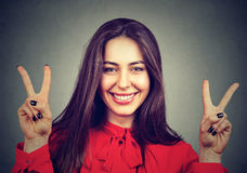 Smiling woman showing peace hand sign with both hands. Smiling young woman showing peace hand sign with both hands royalty free stock photo