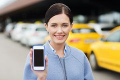 Smiling woman showing smartphone over taxi in city. Travel, business trip, people and tourism concept - smiling young woman showing smartphone blank screen over stock photography