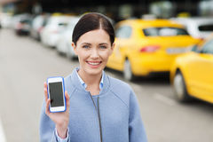 Smiling woman showing smartphone over taxi in city Royalty Free Stock Photo