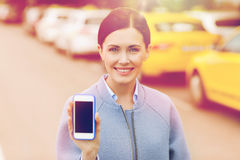 Smiling woman showing smartphone over taxi in city Royalty Free Stock Photos