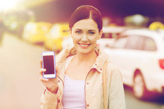 Smiling woman showing smartphone over taxi in city Royalty Free Stock Image