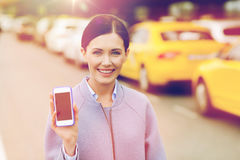 Smiling woman showing smartphone over taxi in city Stock Photography