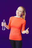 Smiling woman showing a thumbs up sign while holding a bottle of water while standing on a blue background Royalty Free Stock Images