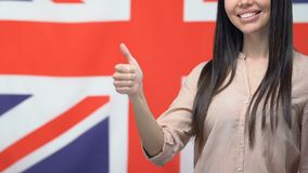 Smiling woman showing thumbs up, standing against British flag, studying English. Stock footage stock video