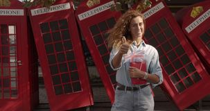 Smiling woman showing thumbs up, standing against British telephone, studying English.