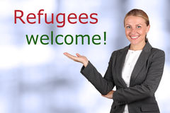 Smiling woman showing to sign welcome refugees. Blue background behind stock images