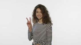 Smiling woman showing v sign on white background. Positive girl show v gesture stock video footage