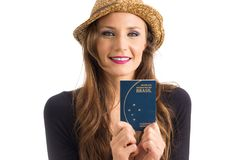 Smiling woman shows her passport. Person with green eyes and blo. Brazilian passport in the hands of a beautiful woman. Wearing panama hat. Person wears black Royalty Free Stock Photos