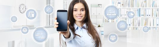 Smiling woman shows smartphone with business icons on i stock photo