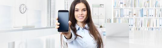 Smiling woman shows smartphone isolated on interior office business background stock image