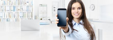 Smiling woman shows smartphone isolated on interior office business background royalty free stock photos