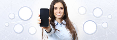 Smiling woman shows smartphone, social media, social network. Concept Stock Photography