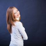 Smiling woman sidewise with crossed arms. Studio shot of young caucasian smiling woman standing sidewise with crossed arms Royalty Free Stock Photo