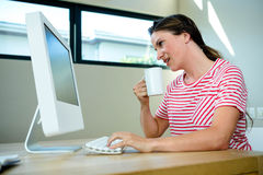 smiling woman sipping coffee at her desk Royalty Free Stock Photography