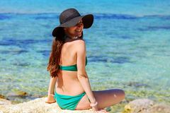 Smiling woman sits on the beach half-turn and looks at the camera. in green swimsuit and hat.  Royalty Free Stock Photos
