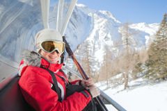The smiling woman sits at chair lift on mountain resort Royalty Free Stock Image