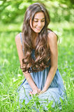 Smiling woman sits on green grass Royalty Free Stock Image