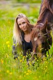 Smiling woman sits in the meadow with her arabian horse Stock Image