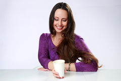 Smiling woman sittin at the table with beverage Royalty Free Stock Photo