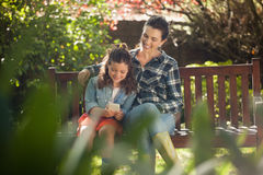 Smiling woman sitting with arm around daughter using mobile phone on wooden bench Royalty Free Stock Photography