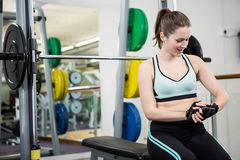 Smiling woman sitting on barbell bench royalty free stock photography