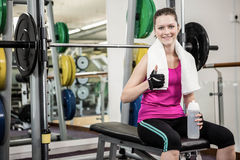 Smiling woman sitting on barbell bench and showing thumb up Royalty Free Stock Image