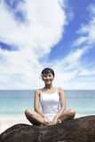 Smiling woman sitting at beach Royalty Free Stock Images