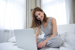 Smiling woman sitting on the bed with laptop Royalty Free Stock Images