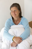 Smiling woman sitting in bed Stock Photography