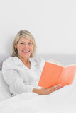 Smiling woman sitting in bed reading Royalty Free Stock Photo
