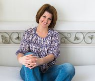 Smiling woman sitting in bedroom on bed Stock Images