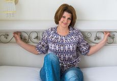 Smiling woman sitting in bedroom on bed Stock Photography