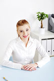 Smiling woman sitting behind the desk Stock Photo
