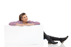 Smiling Woman Sitting Behind Poster Royalty Free Stock Photography