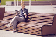 Smiling woman sitting on a bench with coffee and reading magazin Stock Photo