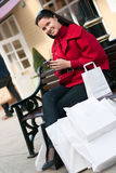Smiling woman sitting on the bench after shopping Royalty Free Stock Image