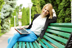 Smiling woman sitting on the bench Royalty Free Stock Photography