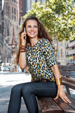 Smiling woman sitting on a bench and talking smartphone Royalty Free Stock Photo