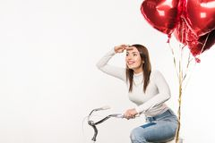 Woman sitting on bike with balloons. Smiling woman sitting on bike with red balloons and looking away isolated on white Royalty Free Stock Images