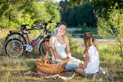 Smiling woman sitting on blanket under big tree with her daughte Stock Photo